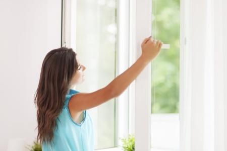 換気のために窓を開ける女性