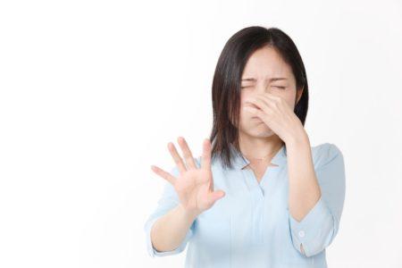 鼻をつまんで拒絶する女性