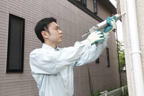 コーキング剤を塗布・注入しひび割れ箇所を補修している作業員