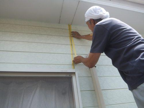 コーキング剤で白色の壁のひび割れを補修している作業員