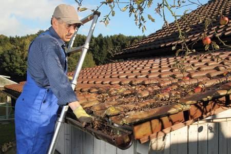 雨樋を掃除する男性