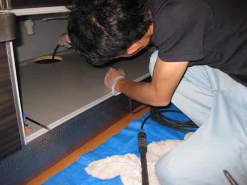 排水管に高圧洗浄機を入れる作業員