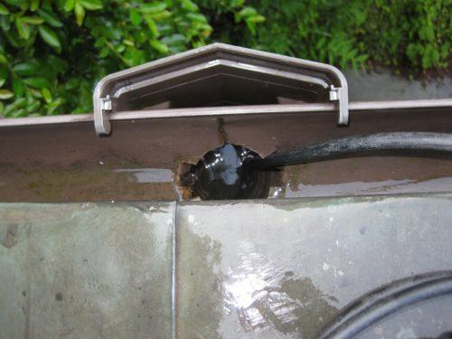 雨樋の管内にこびり付いた泥などを高圧洗浄機で清掃している様子