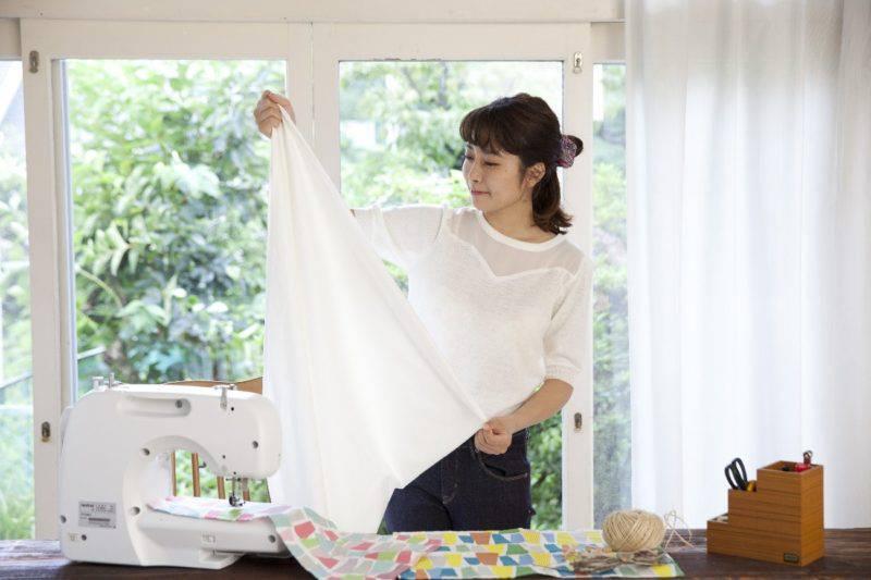 カーテンを縫う女性