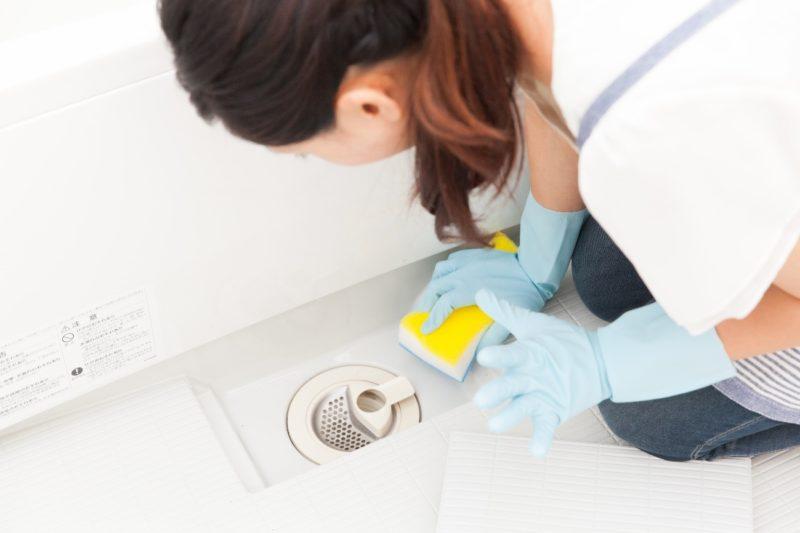 浴室排水口黄色スポンジで洗浄中