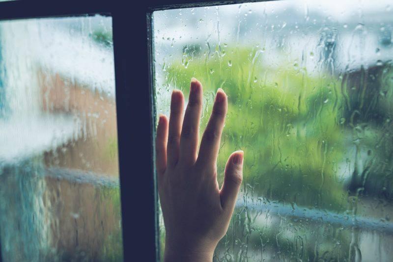 雨に濡れる窓と手