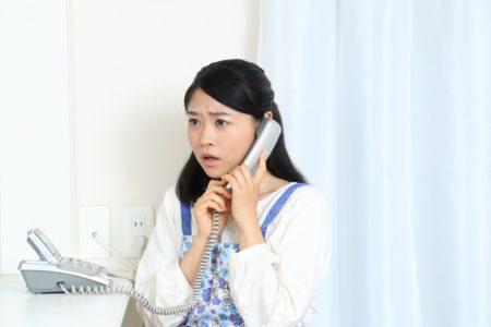 電話をかけるエプロン女性