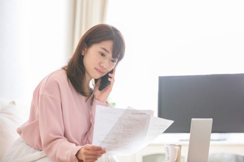 書類を手に電話する女性